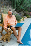 Picture of a senior man petting his dog by the pool. He is bald, is wearing headphones, and has a laptop computer in his lap. The older man is barefoot and sitting in a lounge chair next to the swimming pool.